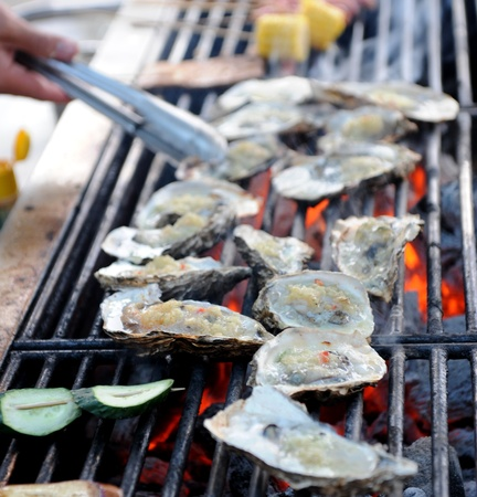 many fresh oyster on fire. Stock Photo
