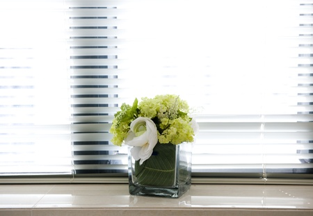 sill: A bouquet of flowers standing on the window sill windows closed shutters.  Stock Photo