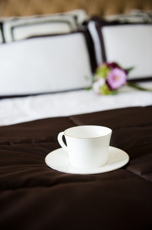 Luxury bedding with cup and flower.   photo