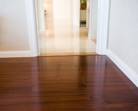 skirting: Corner of an empty room with wooden floor boards.