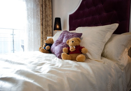 Close up of teddy bear in bed photo