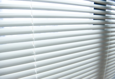a blind: background image of white mini blinds inside home closed.  Stock Photo