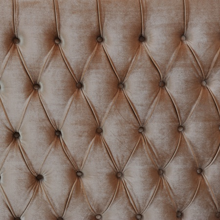 brown button-tufted leather background.