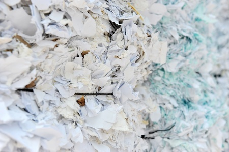 unreadable: stack of shredded paper at recycling plant.