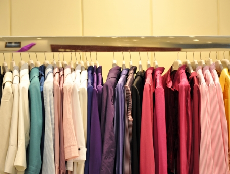 racks: Colorful collection of womens clothes hanging on a rack. Stock Photo