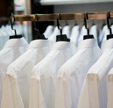 lavanderia: hilera de perchas de tela con las camisas Foto de archivo