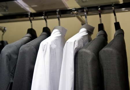 row of cloth hangers with shirts and suit. photo