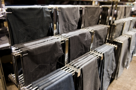 togs: trousers on hangers at the show, for sale.  Stock Photo
