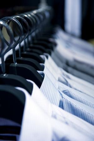 ropa colgada: hilera de perchas de tela con las camisas Foto de archivo