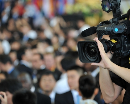 live action: Live broadcasting, television operator with camera. Selective focus on hand