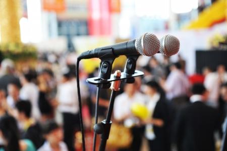 orator: Closeup microphone in auditorium with people. Editorial