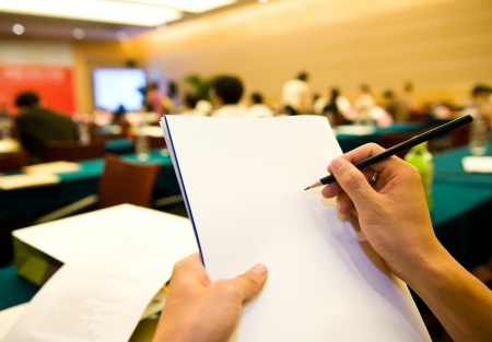 lecture room: people writing on the document in a business seminar.