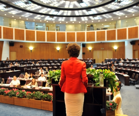 conference hall: Business woman is making a speech in front of a big audience at a conference hall.