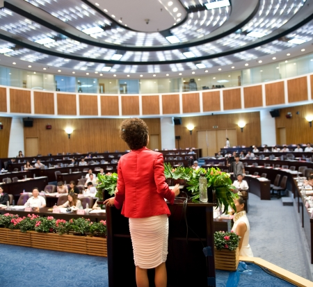 predicador: Mujer de negocios que está haciendo un discurso frente a una gran audiencia en una sala de conferencias. Editorial