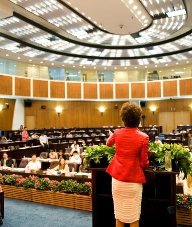 delegar: Mujer de negocios que est� haciendo un discurso frente a una gran audiencia en una sala de conferencias. Editorial