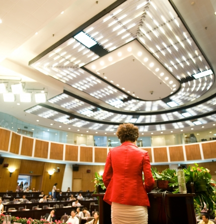 table skirt: Business woman is making a speech in front of a big audience at a conference hall.
