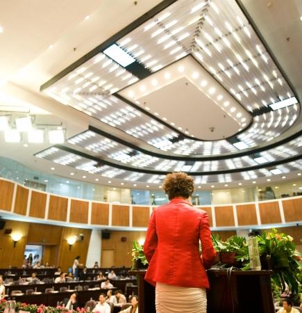 hablar en publico: Mujer de negocios que est� haciendo un discurso frente a una gran audiencia en una sala de conferencias. Editorial