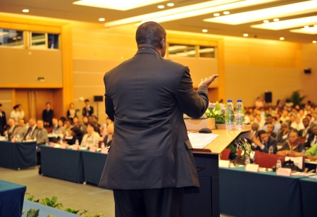 Business man is making a speech in front of a big audience at a conference hall. Stock Photo - 13602344