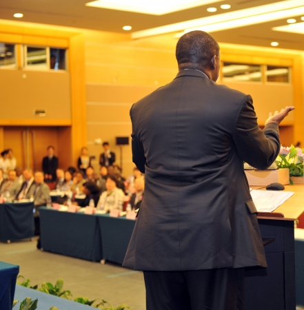 convention: Business man is making a speech in front of a big audience at a conference hall. Editorial