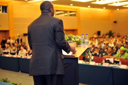 delegate: Business man is making a speech in front of a big audience at a conference hall. Editorial