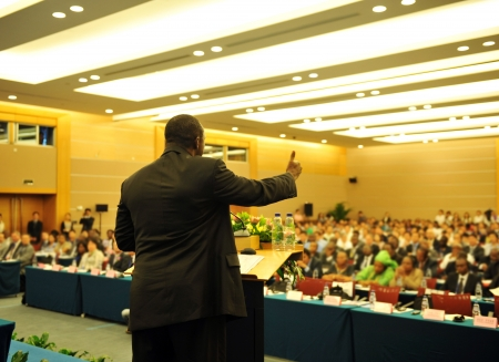 Business man is making a speech in front of a big audience at a conference hall.