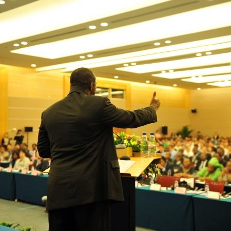 predicatore: Uomo d'affari sta facendo un discorso di fronte a un grande pubblico in una sala conferenze. Editoriali