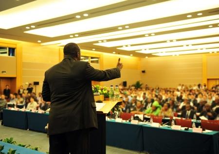 delegar: Hombre de negocios que est� haciendo un discurso frente a una gran audiencia en una sala de conferencias. Editorial
