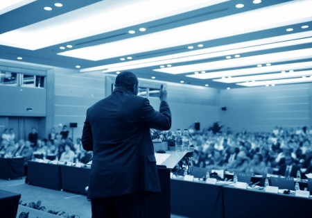 conference audience: Business man is making a speech in front of a big audience at a conference hall. Editorial