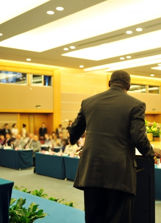 Business man is making a speech in front of a big audience at a conference hall. Stock Photo - 13602170