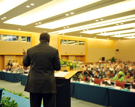 Business man is making a speech in front of a big audience at a conference hall. Editorial