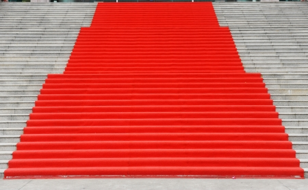 Red carpet on marble stairway welcoming VIPs. photo