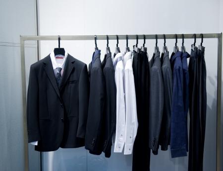 ropa colgada: Fila de los trajes de los hombres que cuelgan en el armario.
