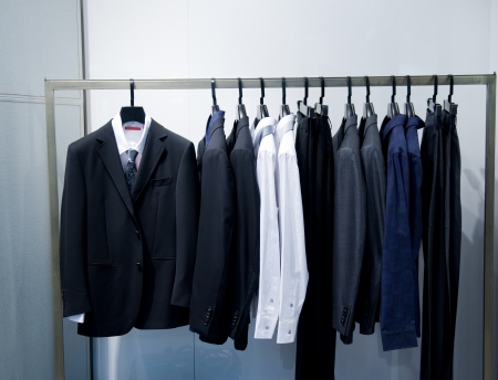 laundry hanger: Row of mens suits hanging in closet.