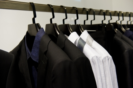 Row of mens suits hanging in closet. photo