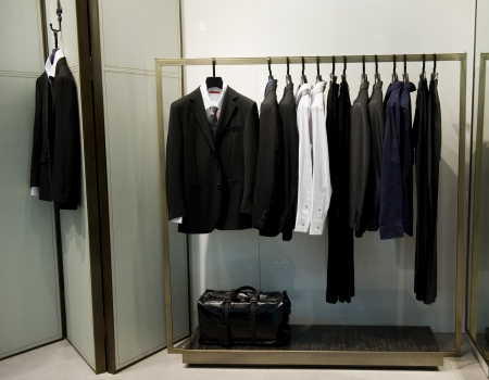 Row of men's suits hanging in closet. photo