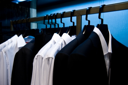 formal attire: Row of mens suits hanging in closet.