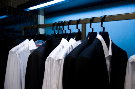 tailored: Row of mens suits hanging in closet.