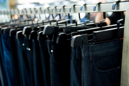 Row of hanged blue and black jeans in a shop   photo