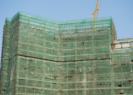 Green net covering scaffoldings of an under construction building photo