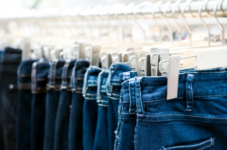 clothing rack: Row of hanged blue jeans in a shop