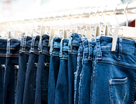 garment industry: Row of hanged blue jeans in a shop