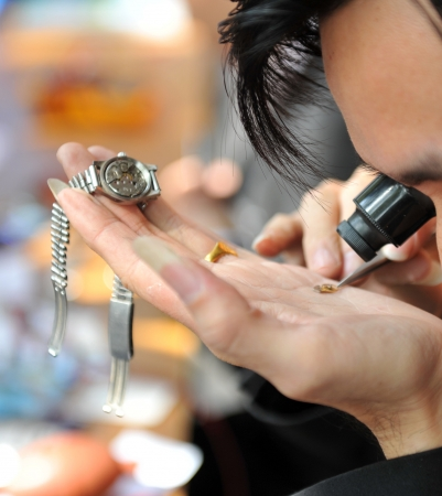 A watchmaker or repair man in action, viewing very closely a watch. photo