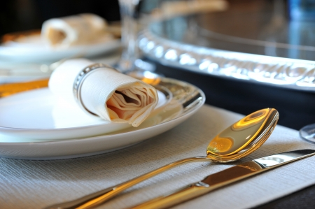 fine gold: fork and knife on a napkin with plate.