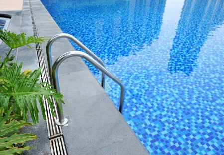 A swimming pool with steel stair.  photo
