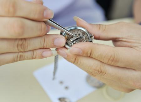 mans watch: Las manos del hombre la reparaci�n de reloj antiguo, la celebraci�n de una pieza con pinzas.