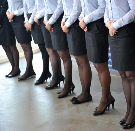 skirt suit: many legs of a businesspeople sanding together.