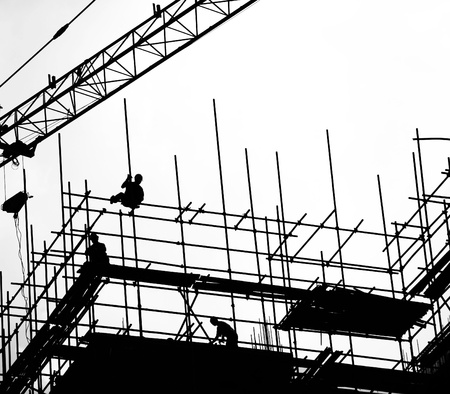 girders: Construction workers working on scaffolding