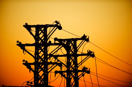 electric grid: high voltage post at sunset.