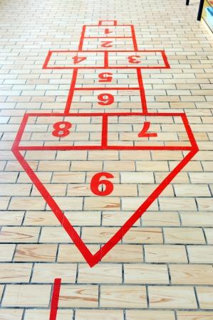 saltar: Juego de la rayuela pintada en el pavimento de la escuela.