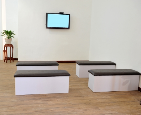 waiting area: Hospital or clinic waiting room with stools and flat screen TV. Stock Photo